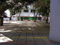 A quadrangle with checkered tiles in colour, with a dias, many trees and green doors
